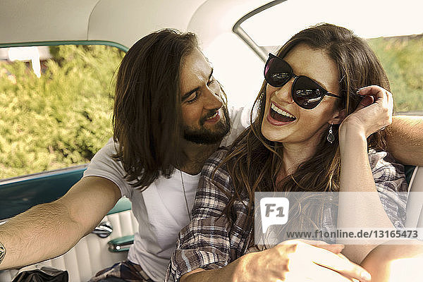 Young couple laughing in back seat of car