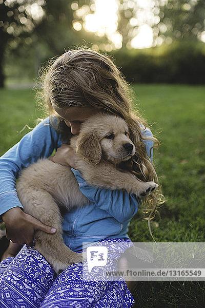 Girl hugging puppy in garden at sunset