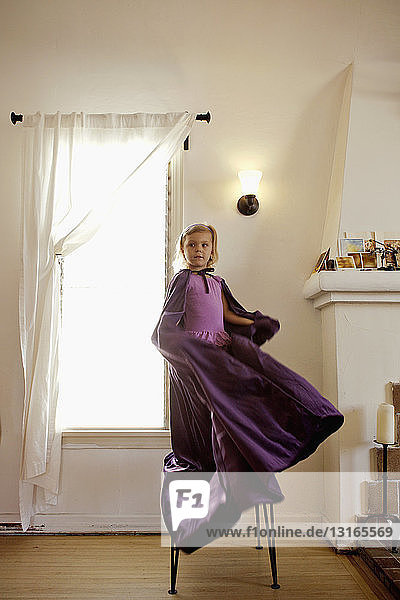 Porträt eines jungen Mädchens  das auf einem Stuhl steht und einen langen Umhang schwingt