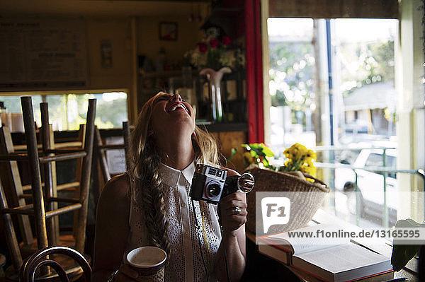 Junge Frau mit Kamera im Cafe