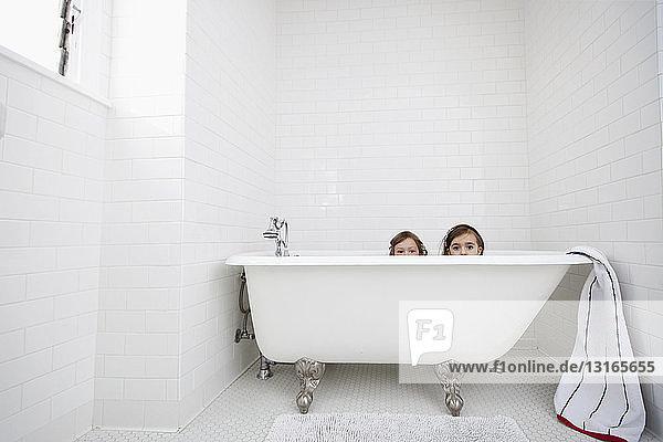 Porträt von zwei jungen Mädchen  die über der Badewanne spähen