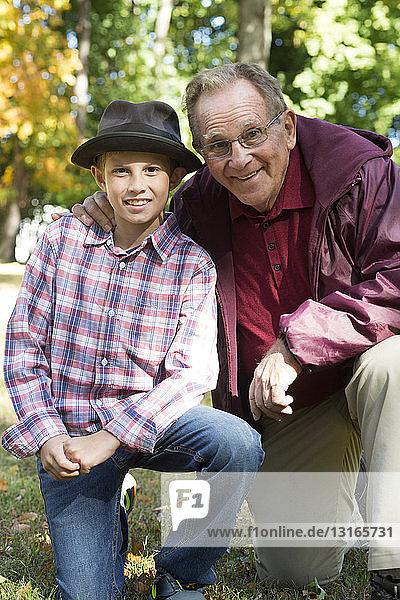 Porträt eines älteren Mannes und seines Enkels kniend im Wald