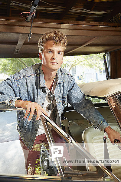 Portrait of young man in garage opening door of vintage car