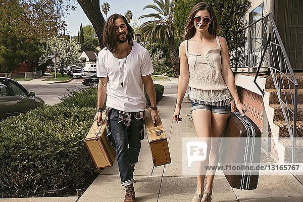 Junges Paar mit Koffern auf der Straße