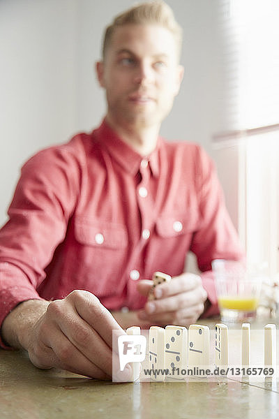 Man placing domino on edge