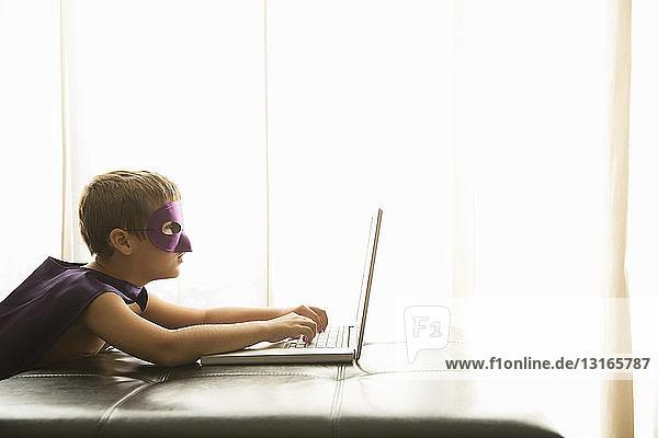 Junge mit Umhang und Maske mit Laptop zu Hause