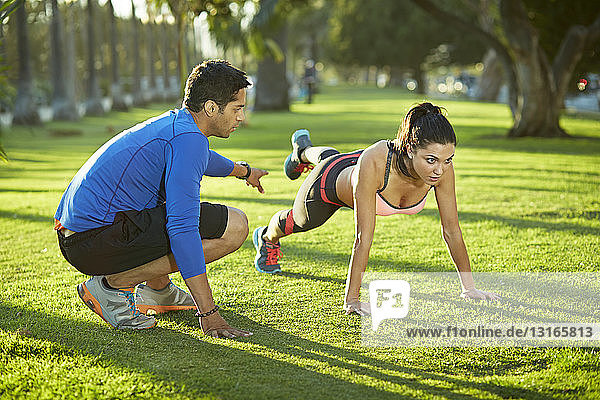 Personal trainer with woman doing plank exercise