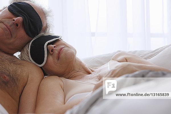 Älteres Ehepaar schläft mit Gesichtsmasken im Bett