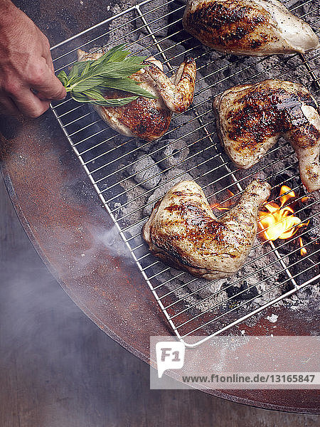 Mans hand grilling Guam chicken legs on barbecue