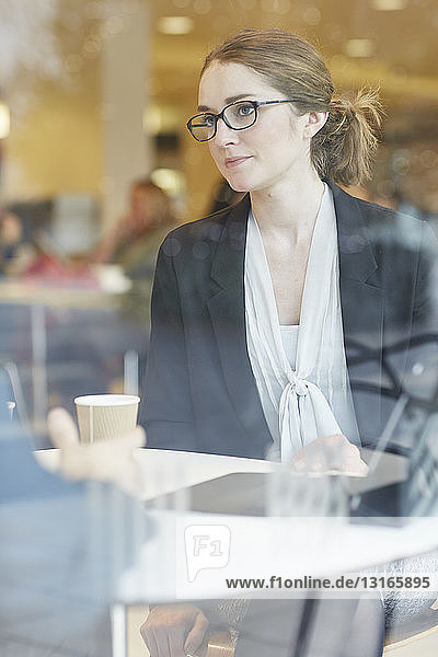 View through window of businesswoman wearing eye glasses sitting at table looking at colleague