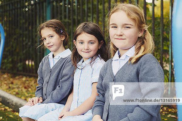 Portrait of three elementary schoolgirls in playground