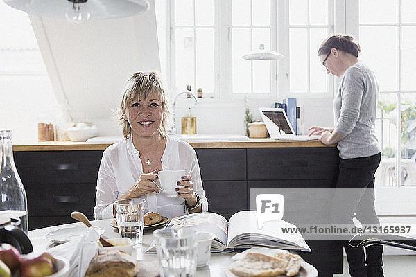 Porträt einer reifen Frau  die am Tisch sitzt und ein heißes Getränk hält