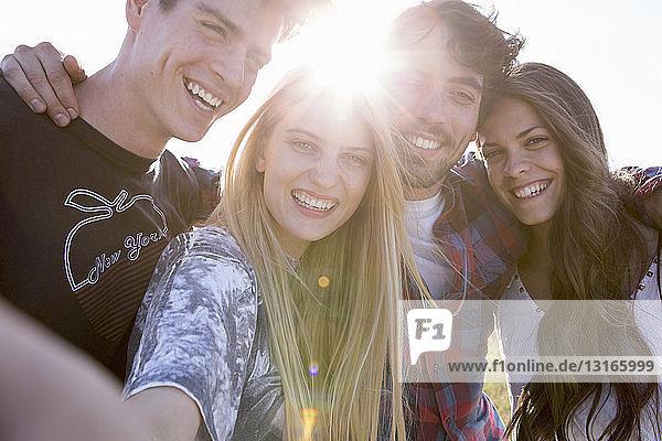 Vier Freunde lächeln in die Kamera