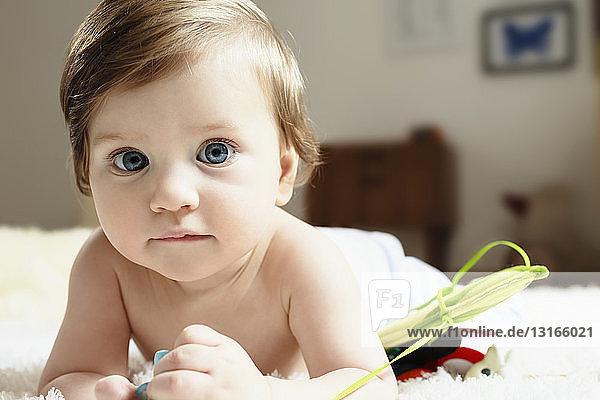 Porträt eines kleinen Jungen  der auf der Vorderseite liegt und in die Kamera schaut
