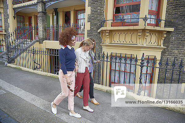Side view of friends walking down residential street arm in arm smiling  Shoreditch  London