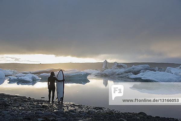 Frau mit Surfbrett  Jokulsarlon-Gletscherlagune  Skaftafell-Nationalpark  Island