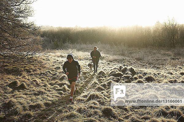 Hochwinkel-Frontansicht von Mutter  Sohn und Hund beim Laufen auf Grasland
