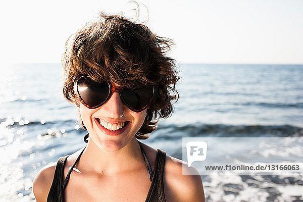 Lächelnde Frau mit Sonnenbrille am Strand