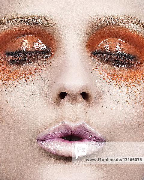 Junge Frau mit orangefarbenem Augen-Make-up  Nahaufnahme
