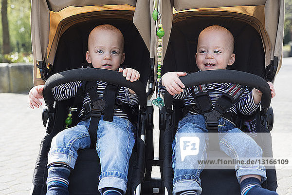 Portrait of baby twin brothers in pushchairs at park