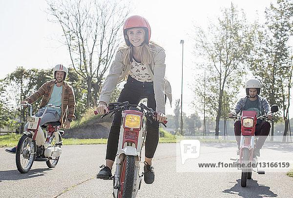 Eine Gruppe von Freunden fährt mit Mopeds entlang der Straße  im Vordergrund eine junge Fahrerin