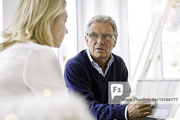 Paar sitzt und diskutiert über Papierkram