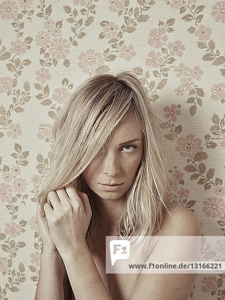 Portrait of young woman  nude  against floral wallpaper