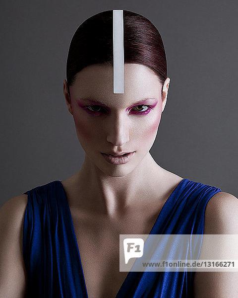 Porträt einer jungen Frau mit schwerem Augen-Make-up und Streifen in der Mitte des Kopfes