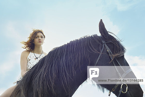 Portrait of young woman on horse