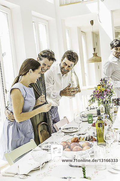 Ehepaar und erwachsene Tochter bereiten Esszimmertisch für Party vor
