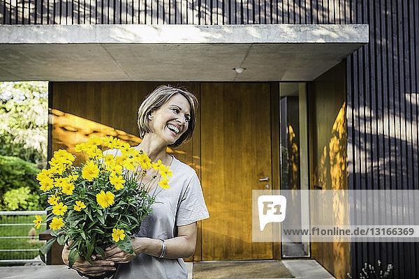 Reife Frau vor neuem Haus mit gelbem Blumentopf