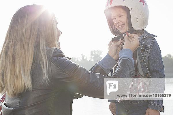 Junge Frau setzt der Tochter einen Sturzhelm auf und lächelt