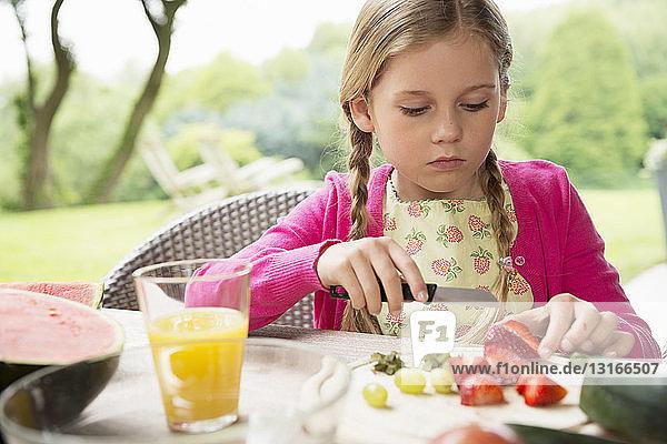 Girl at patio table slicing fresh strawberries