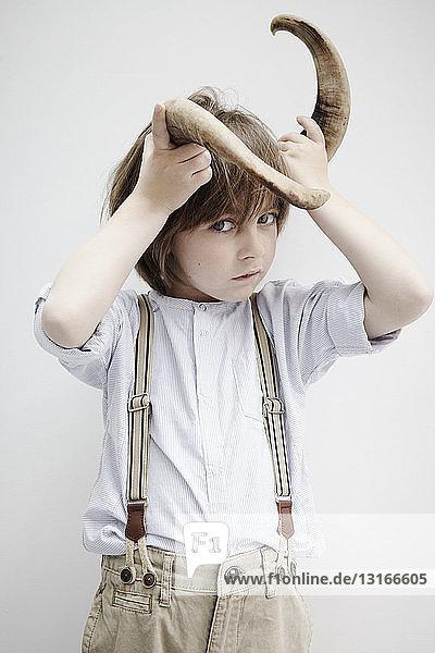 Boy posing with animal horn