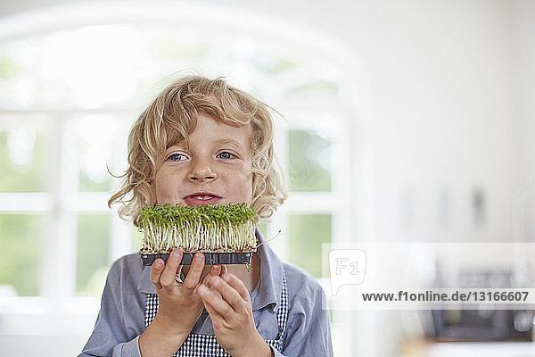 Junge spielt mit Gemüse in der Küche