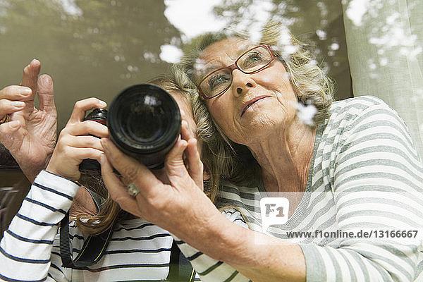 Grandmother teaching granddaughter camera usage
