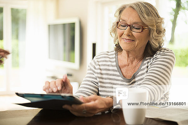 Senior woman reading using digital tablet