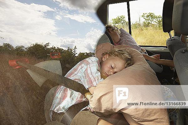 Zwei schlafende Jungen auf dem Rücksitz eines Geländewagens