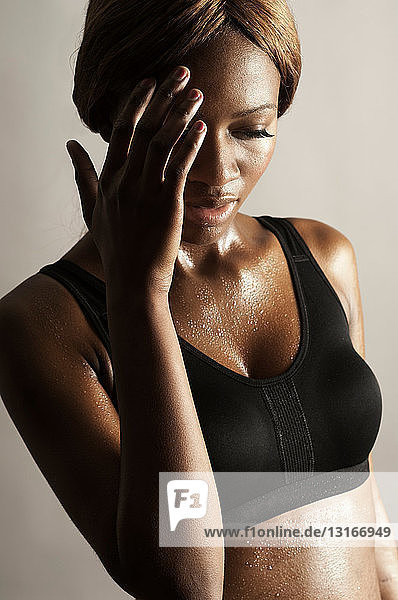 Studio shot of woman with hand on face