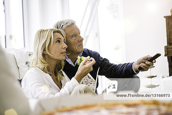 Side view of couple sitting on sofa eating salad watching television