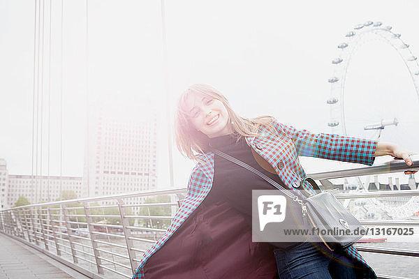 Porträt einer jungen Touristin  die sich auf der Fußgängerbrücke zum Golden Jubilee schwingt  London  UK