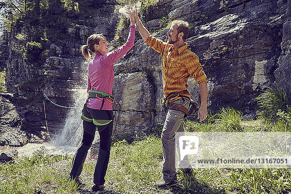 Bergsteiger geben High Five  Wasserfall im Hintergrund  Ehrwald  Tirol  Österreich
