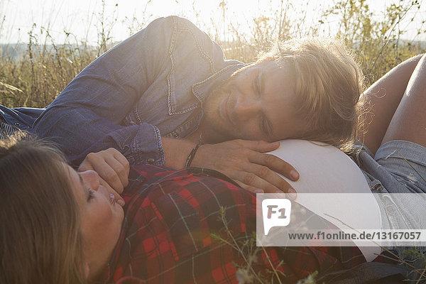 Junger Mann hört schwangeren Freundinnen auf dem Feld beim Bauchen zu