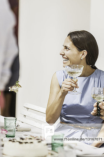 Young woman drinking wine at party