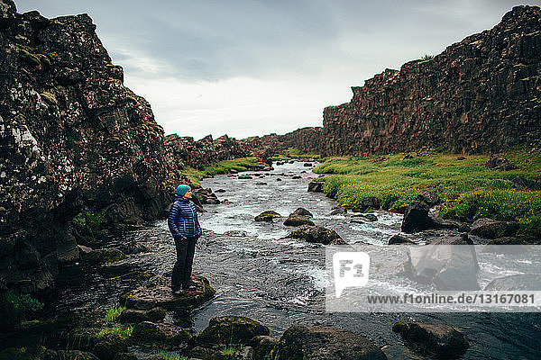 Mittelgroße erwachsene Frau steht auf einem Felsen im Flussbett und schaut weg  Island