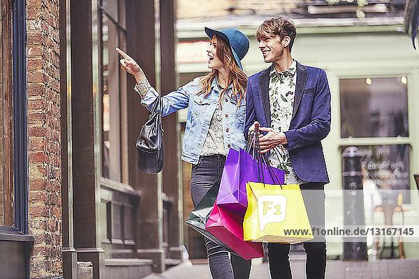 Stylish couple pointing at shop window  London  UK
