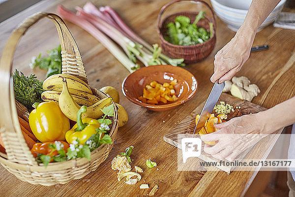Reife Frau beim Gemüseschneiden  Konzentration auf die Hände