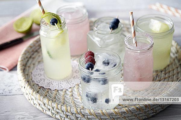Schale mit eisgekühlten Frischobstgetränken in Gläsern mit Trinkhalmen Schale mit eisgekühlten Frischobstgetränken in Gläsern mit Trinkhalmen