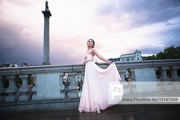 Porträt einer jungen Frau im Abendkleid in der Abenddämmerung  Trafalgar Square  London  UK