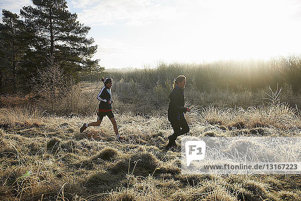 Side view of mother and sons running on frosty grassland
